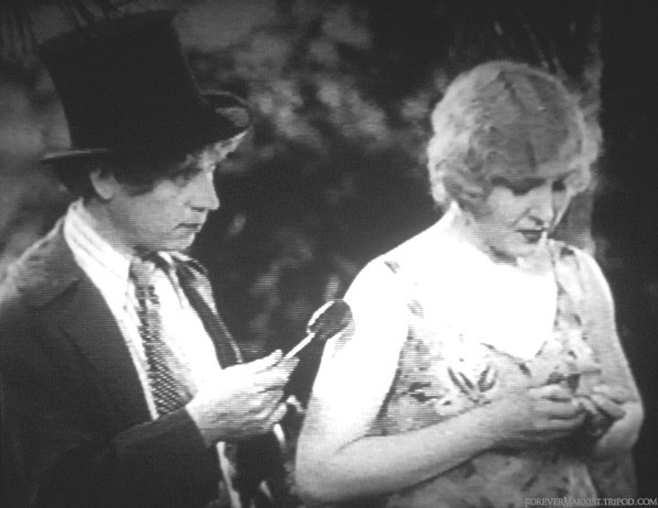the woman is weeping, so harpo tries to make her feel better by giving her a lolly. she doesn't accept.